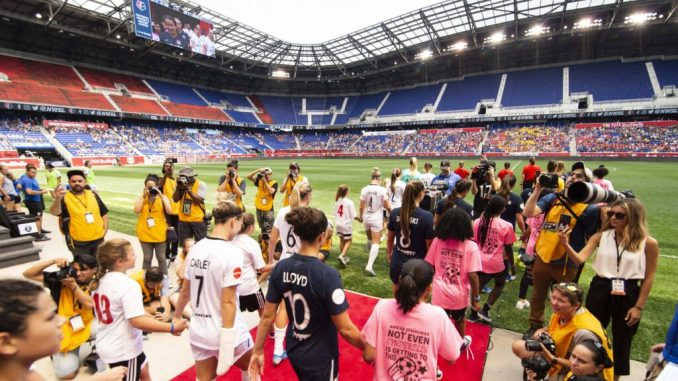 Players from Sky Blue FC and Reign FC walk onto the pitch at Red Bull Arena.