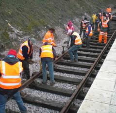 Volunteers lifting rails into place at Mountsorrel Station