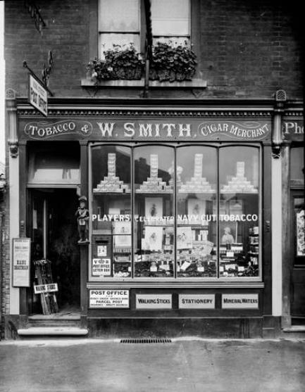 The outside of the 'W. Smith' Post Office in Maidenhead, around 1890. A small post box is attached to the window by the doorframe.