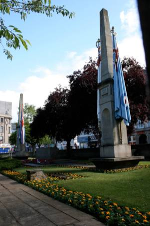 Edwin Lutyens was appointed designer of a new memorial to replace the temporary wooden cenotaph erected in Northampton in 1919. Two tall obelisks, with huge painted stone flags, stand either side of a Stone of Remembrance, a feature which the architect incorporated within a number of his war memorials. An immense crowd attended the unveiling on 11 November 1926, including 5,000 local school children. A large procession preceded the event led by survivors of the Battle of Mons, military and civic representatives and nurses from Northampton General Hospital. Photo courtesy of Tim Skelton