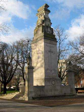 This war memorial was one of the first where Lutyens used the principle of a cenotaph - derived from the Greek 'kenotaphion' meaning empty tomb. It was under design when he created its more famous successor, the Cenotaph in Whitehall, which first appeared in temporary form made of wood, plaster and painted canvas. After having his first Southampton design rejected on cost grounds, Lutyens designed a cenotaph topped by a stone bier holding a sculpture of a fallen soldier on top of a tall stone pillar. It is combined with his Stone of Remembrance. The Southampton memorial is important as it helped set the context for Lutyens' later designs, although it is unique among them for the amount of carving - not only the city's elaborate coat of arms and wreaths with emblems of the armed services but also the pine cones (symbols of eternity) and the two stern lions that guard the bier. At the unveiling on 6 November 1920 the cover encasing the memorial was first pulled away, before the Union Flag was removed to reveal the recumbent soldier. In the months following the dedication, many families campaigned for the names of their dead loved ones to be included - 203 names in total were initially missing. A local stone mason carved them for free, completing the work by 15 November 1921. Over the years, the inscriptions began to erode and, in 2011, green glass panels etched with all the names of the fallen were erected either side of the memorial.