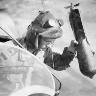 A crew member of an RNAS airship about to drop a bomb from the rear cockpit of the gondola. Image © IWM Q67695. In the early days of aerial warfare, pilots - who flew in open cockpits, heavily muffled against the cold - had improvised by dropping bombs over the side, throwing grenades at the enemy while flying, or by using their pistols or rifles.