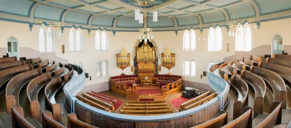 United Reformed Church, High St, Wellingborough. Interior, first floor, showing curved pews on first floor, straight pews on ground floor with organ pipes and central pulpit.