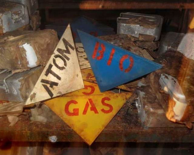 Detail view showing triangular metal signs reading 'gas', 'atom' and 'bio'