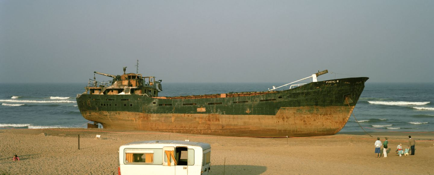 A group of people look at a large ship docked on a beach. There is a small caravan in the foreground