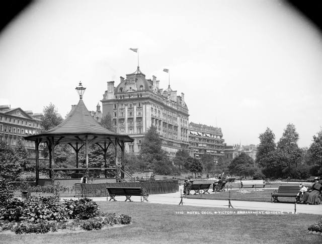 The Cecil Hotel from Victoria Embankment Gardens with a bandstand in the foreground
