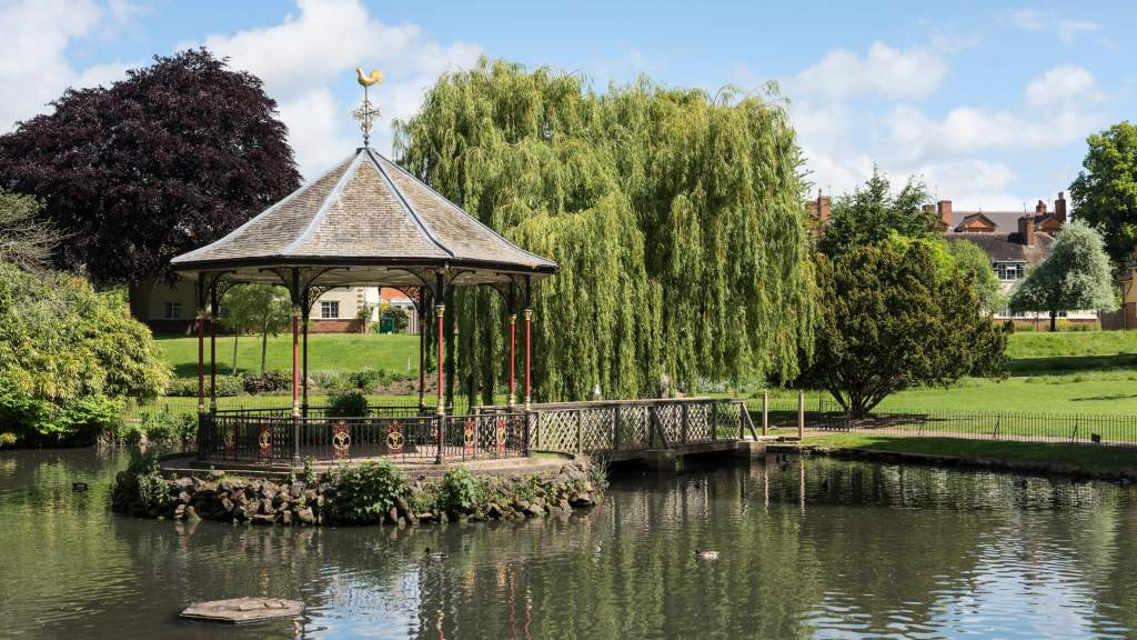 Gheluvelt Park bandstand is surrounded by willow trees, next to a lake
