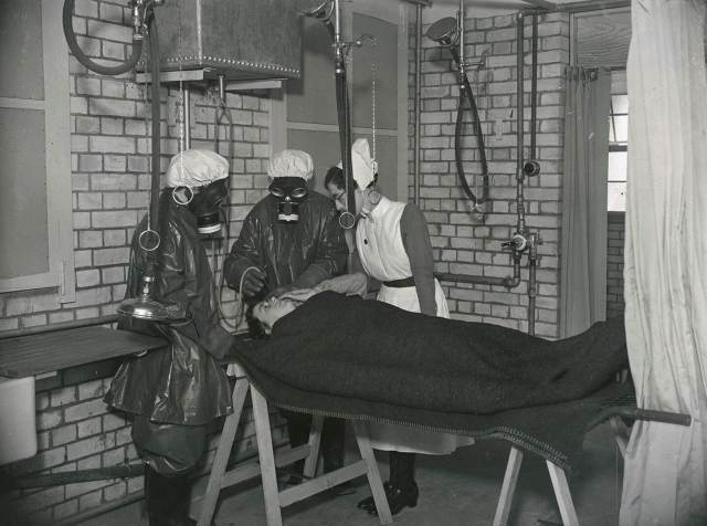 Nurses in protective clothing practising gas decontamination of a patient