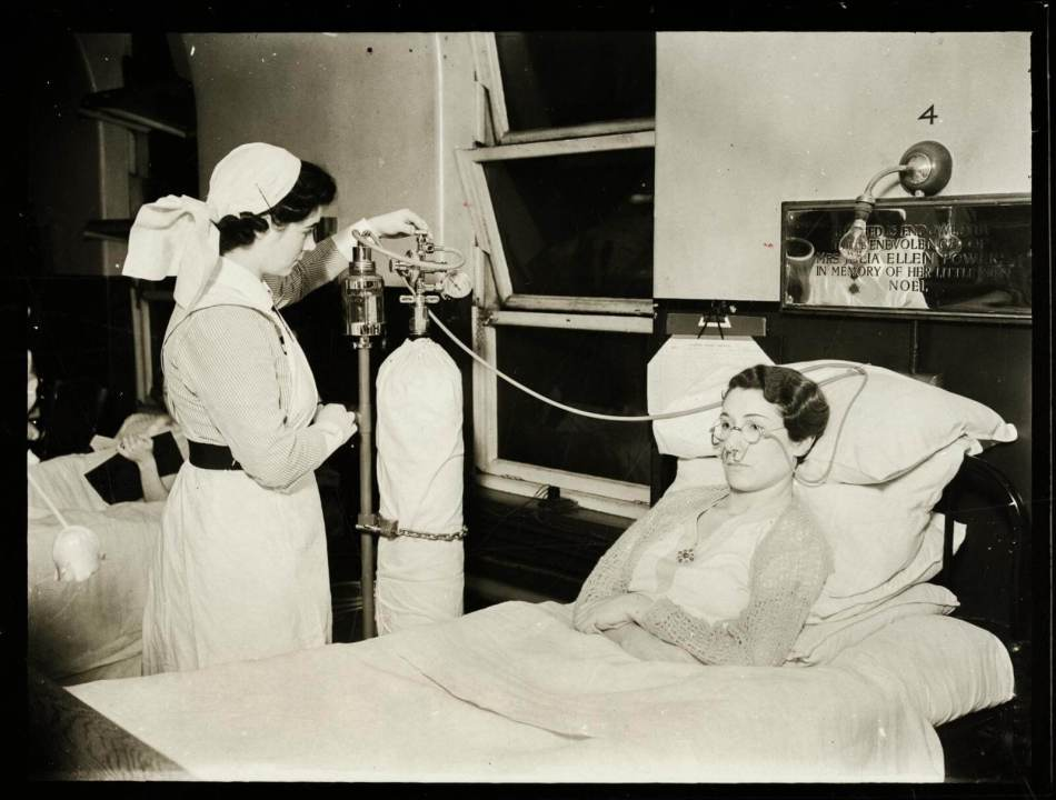 A nurse administering oxygen to a patient wearing Tudor Edwards spectacles