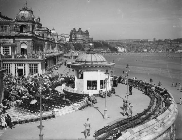 People sit on deck chairs and walk across the promenade surrounding the The Spa Bandstand on the Scarborough coast.