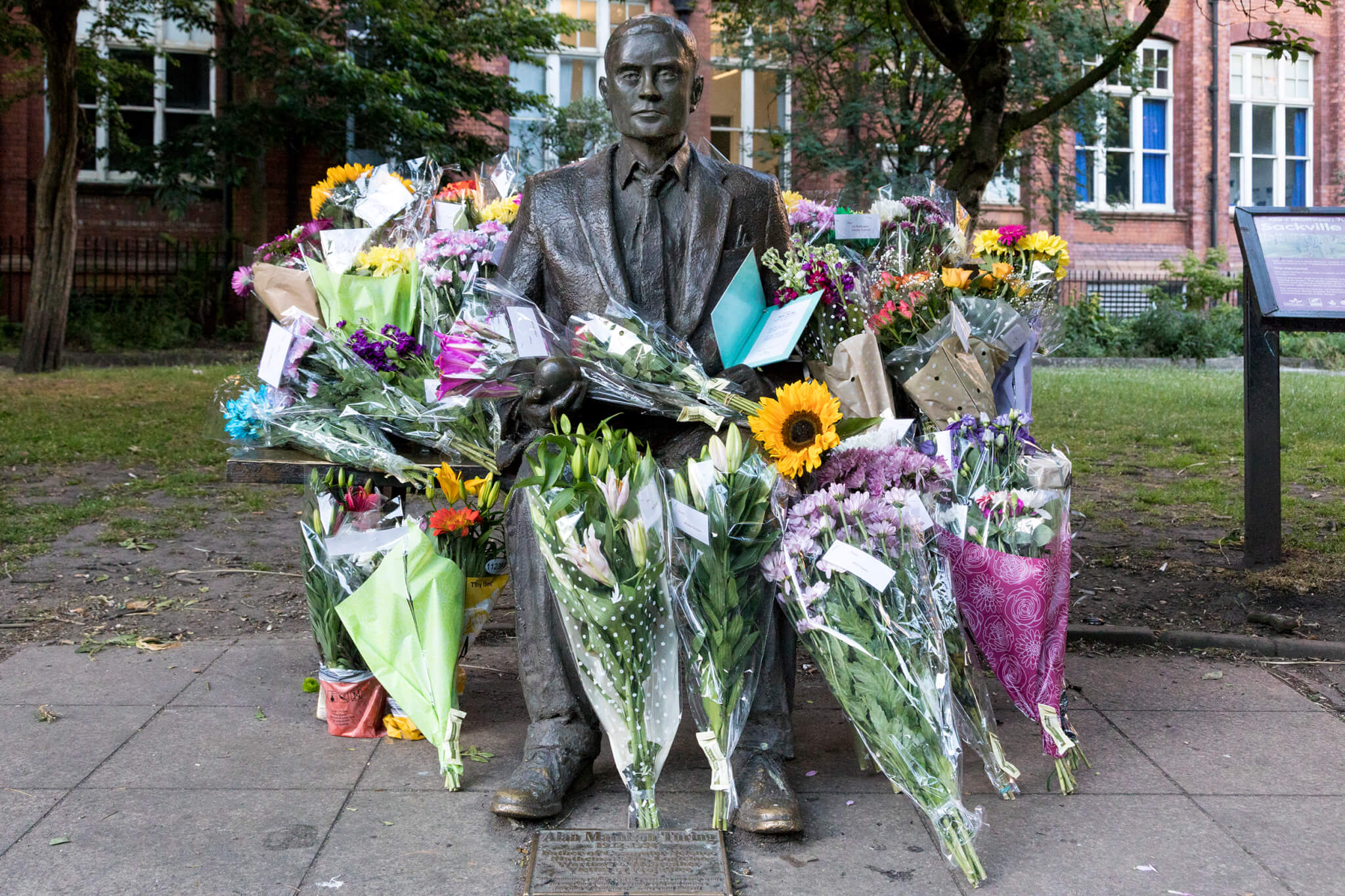 A statue of Alan Turing in Sackville gardens Manchester, surrounded by bouquets of flowers