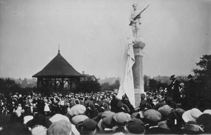 A black and white image of a crowd of people gather as a sheet is pulled to unveil Thurnscoe War Memorial
