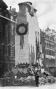 A cenotaph surrounded by wreaths with a guard or soldier stood in front