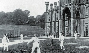 Men play football outside a large gothic style building