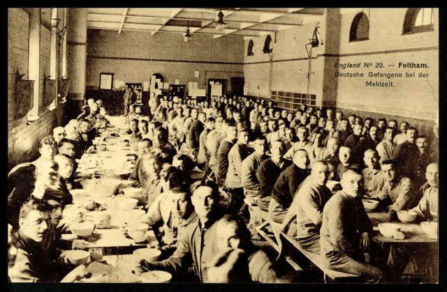 German prisoners of war (POWs) sat at long tables set for a meal