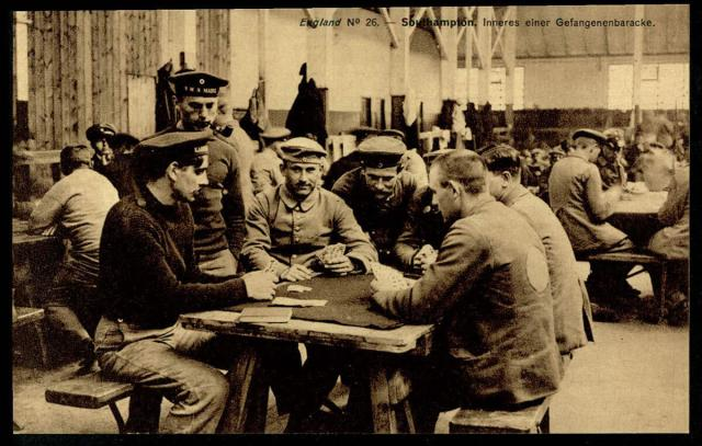 A group of German POWs sit at a table playing cards