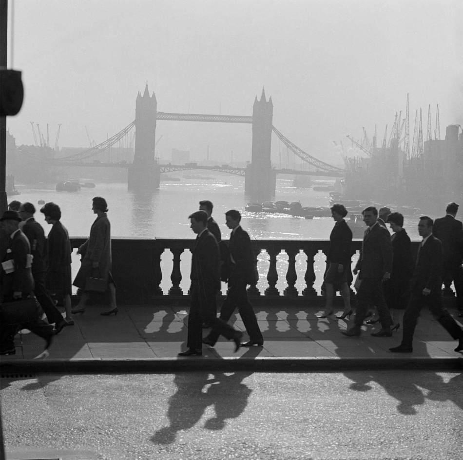 Pedestrians walking across London bridge towards with a view of tower bridge in the haze beyond