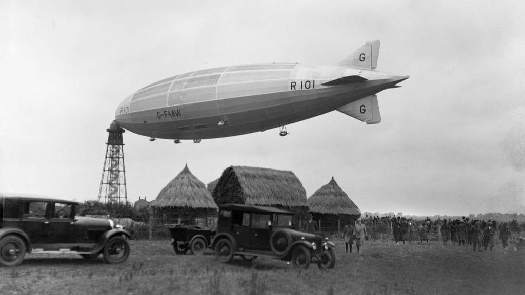 The R101 airship docked, with classic cars in the foreground