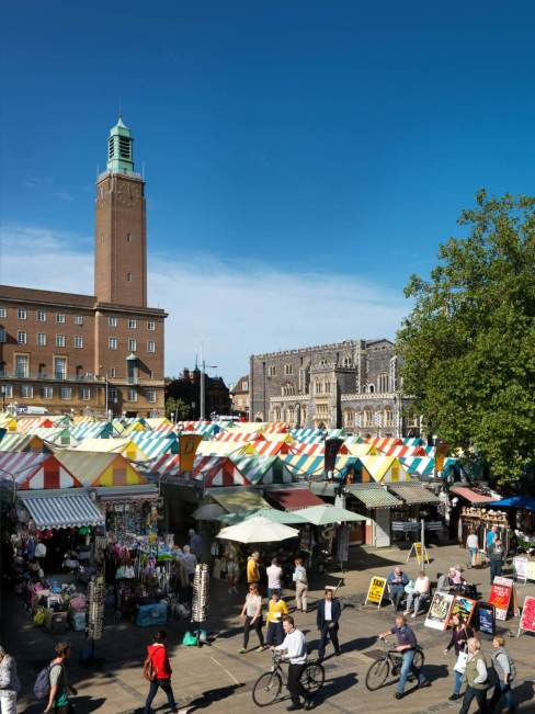 Norwich market from above, with brightly coloured stall covers and people on bicycles