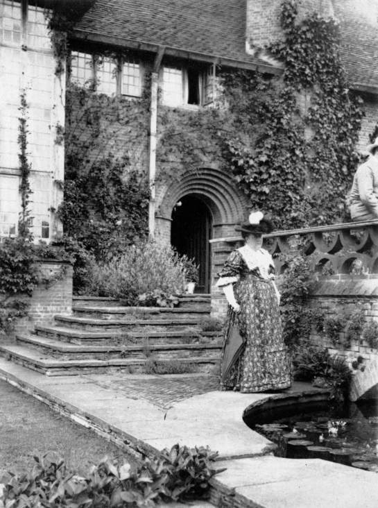 Jekyll pictured in typical Victorian dress and a bonnet, beside a pond in front of a country house