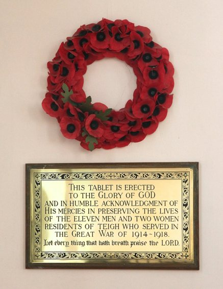 A poppy wreath hangs above a memorial plaque