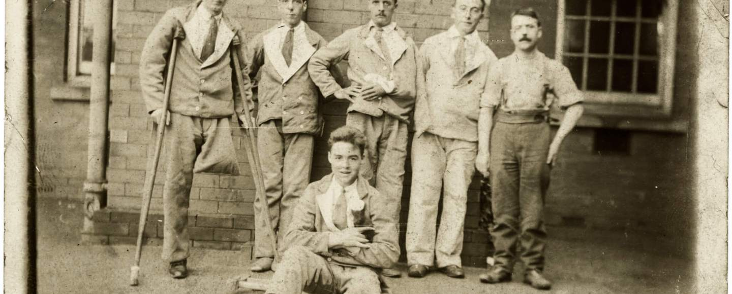 A group of recovering servicemen pose for a picture. One has his arm in a sling and two have amputated legs