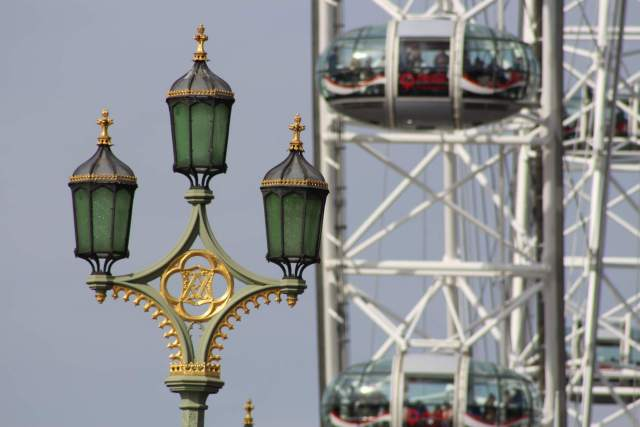 Close up image of decorative lamps on Westminster Bridge, with the London Eye in the background