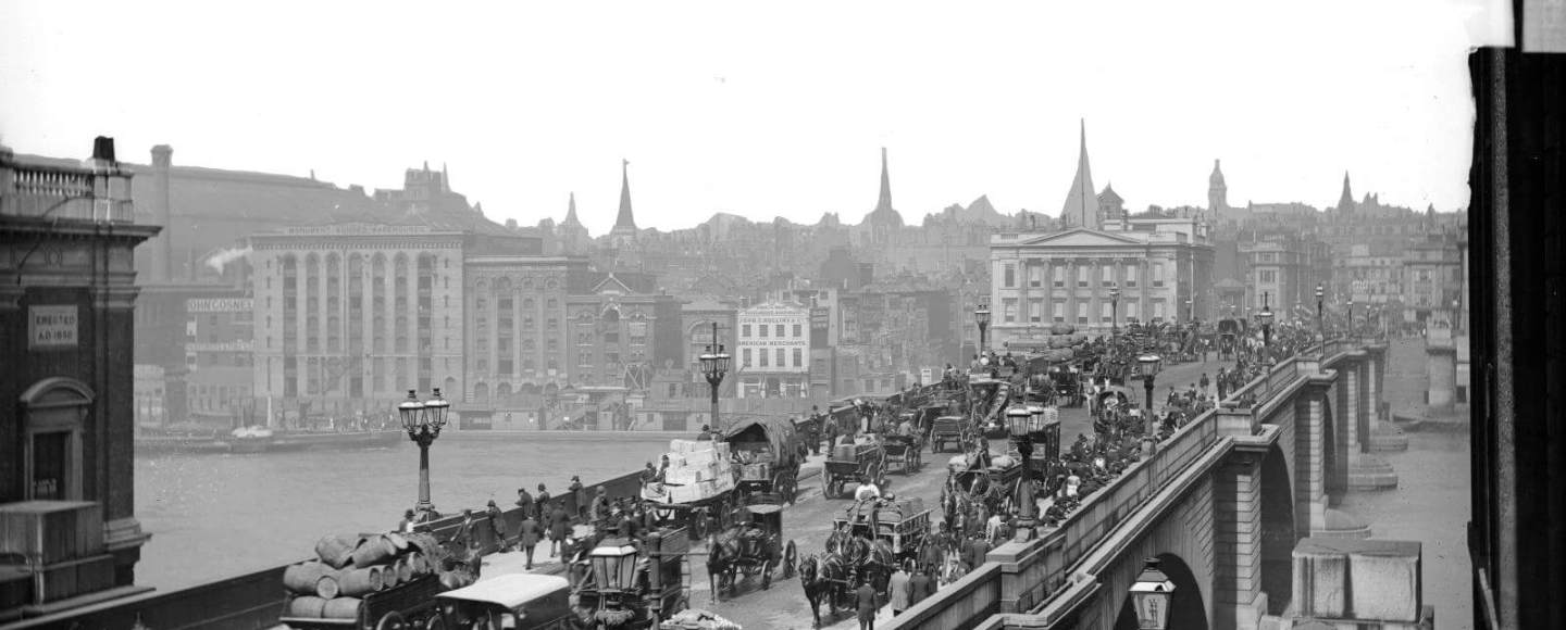 A view looking North West across London Bridge with horse-drawn traffic in the foreground. The bridge was built between 1823 and 1831 by Sir John Rennie.