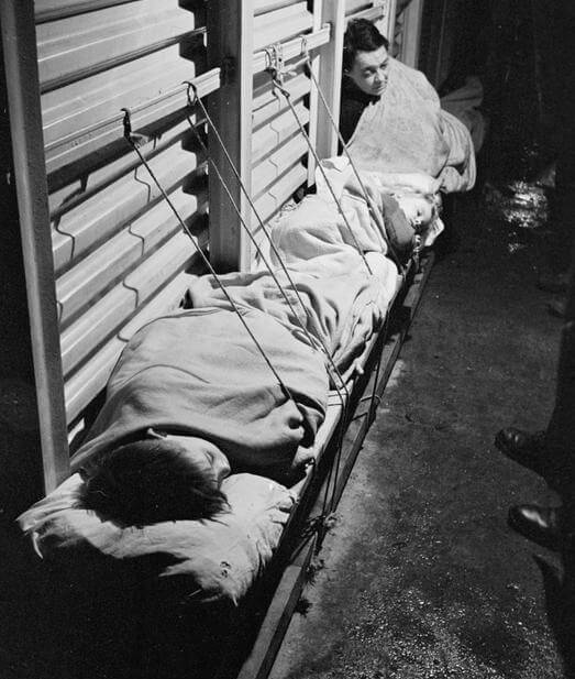 Two children sleep on improvised benches in an air raid shelter