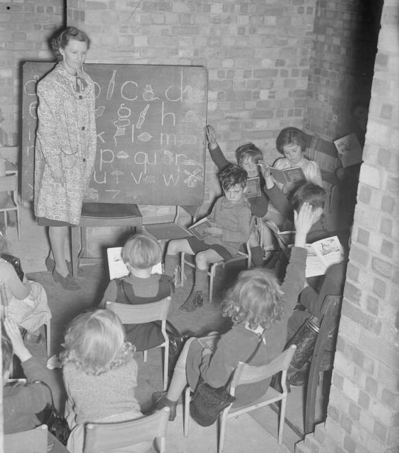 A teacher gives a lesson to infants in a makeshift classroom in the basement of Greek Road School, London