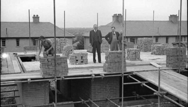 The work of women bricklayers is inspected by foremen as they begin work on the second storey of a house