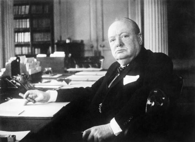 Winston Churchill sits at his seat in the Cabinet Room
