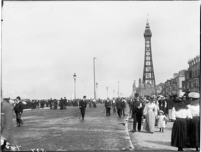 This photograph from 1894 shows holiday makers strolling along the promenade in Blackpool with tall electric lights in the background