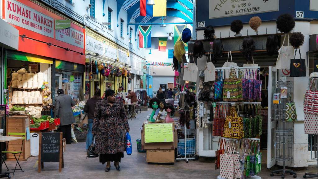 A woman stands in the market with a wig shop on her left and flags above her
