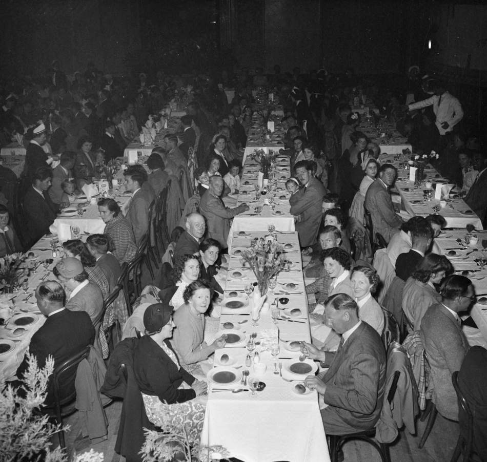 Laing workers with their families eating in a dining hall during a staff outing to Whitley Bay