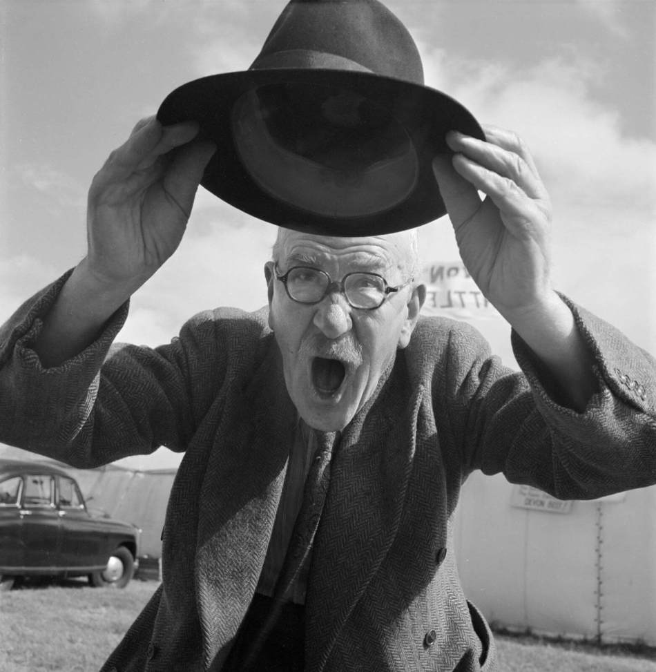 Charlie 'Wardy' Ward, livestock photographer, raising his trilby at the Royal Lancashire Show in Stanley Park, Blackpool, July 1953 © Historic England Archive AA054075