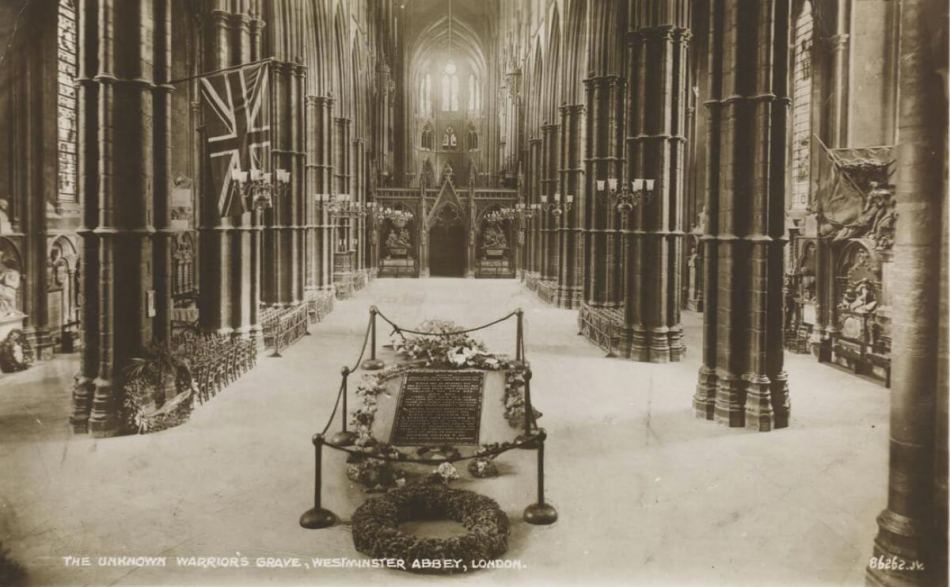 Black and white photo looking along the central aisle of the abbey where a memorial stone is cordoned off by ropes and surrounded by wreaths