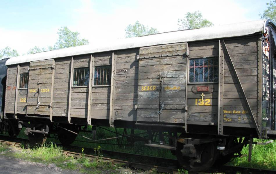Colour photo of an unpainted wooden railway carriage with barred windows.