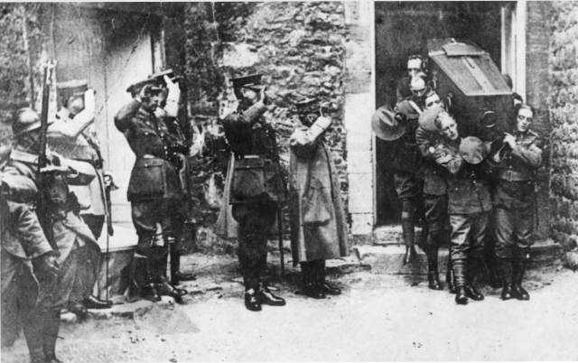 Soldiers bearing the coffin of the Union Warrior exit a door in a stone building. Outside other army colleagues salute the coffin as it appears.