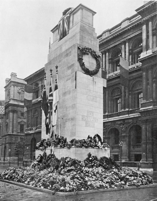 Cenotaph photographed close up showing its base covered in floral tributes, three flags hanging on flagpoles and a union flag draped over the top.