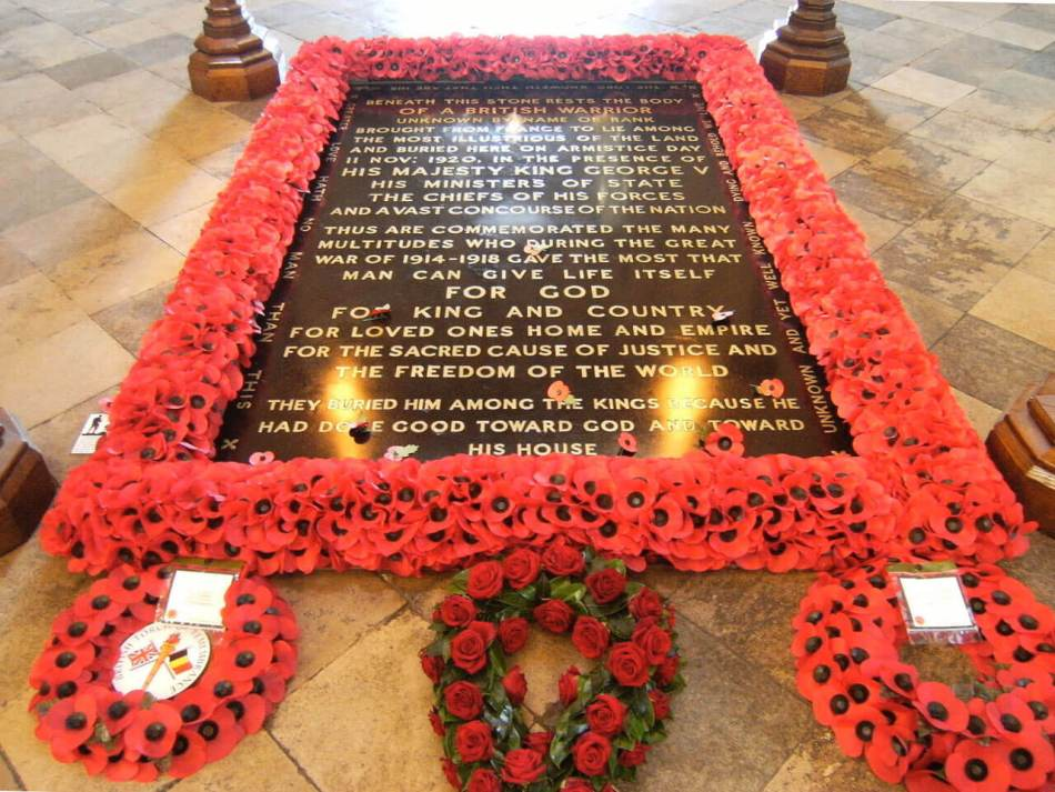 Colour photo of the grave of the Unknown Warrior framed in paper poppies, with three wreaths at the bottom.