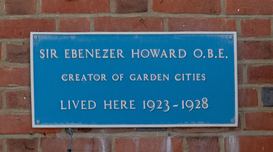 Blue plaque with Sir Ebenzer Howard OBE, Creator of Garden cities, lived here 1923 - 1928, written on it in white text