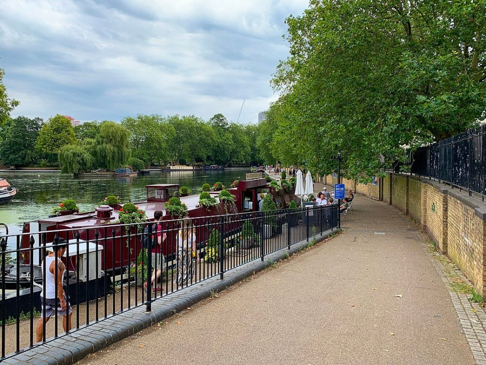 Landscape photograph of Little Venice, looking over the canal from a walkway. A longboat is docked as pedestrians walk by.