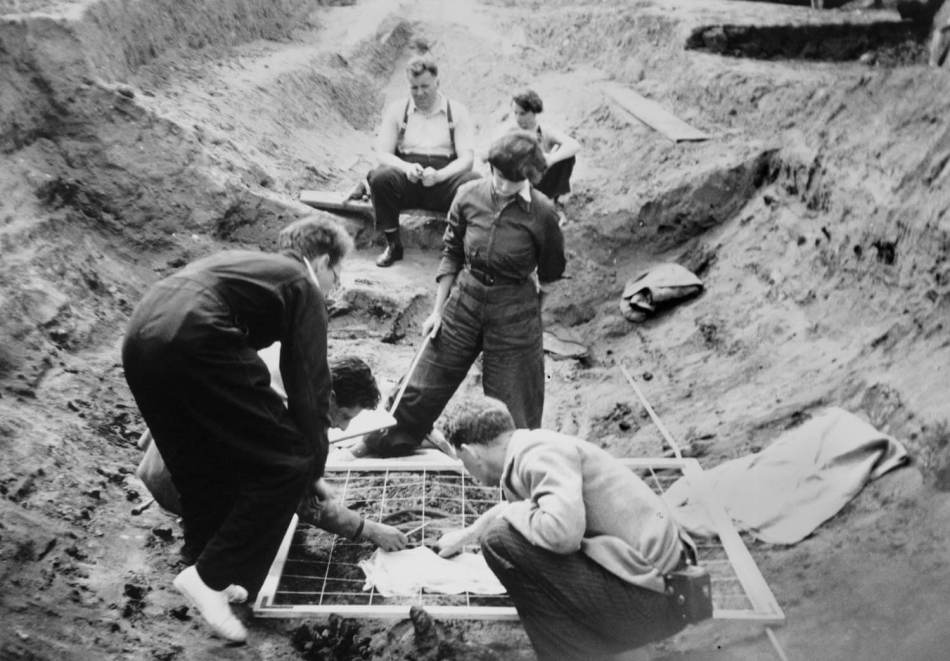 Male and female archaeologists planning artefacts  within a ship burial using a planning frame.
