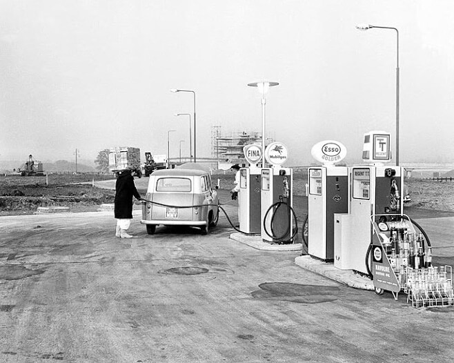 A woman fills up their car at a service station on the M1
