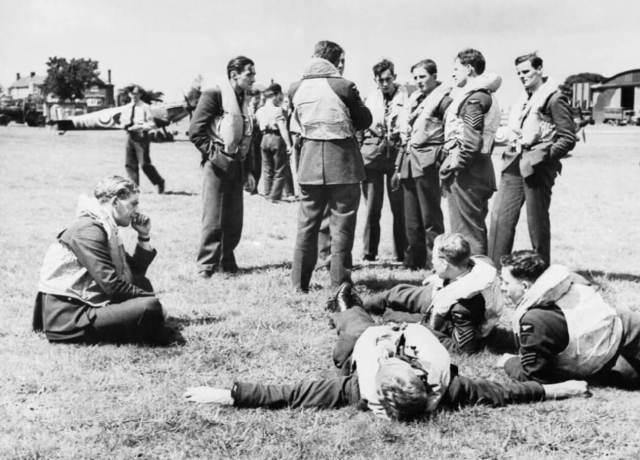 A group of spitfire pilots resting, some sitting on the ground