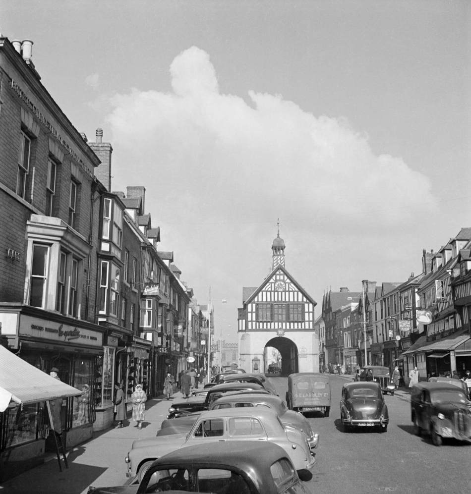 A view of the high street in bridgnorth, shropshire in 1953, looking north towards the timber-framed town hall in the middle of the road.