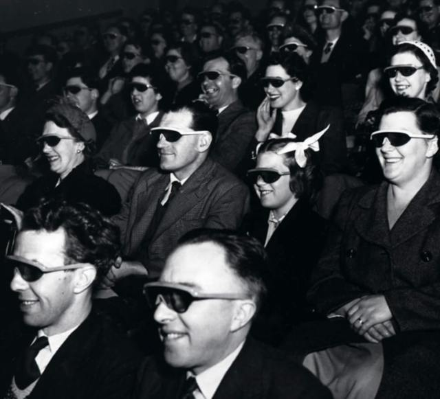 Audience of men and women wearing special sunglasses in the cinema.