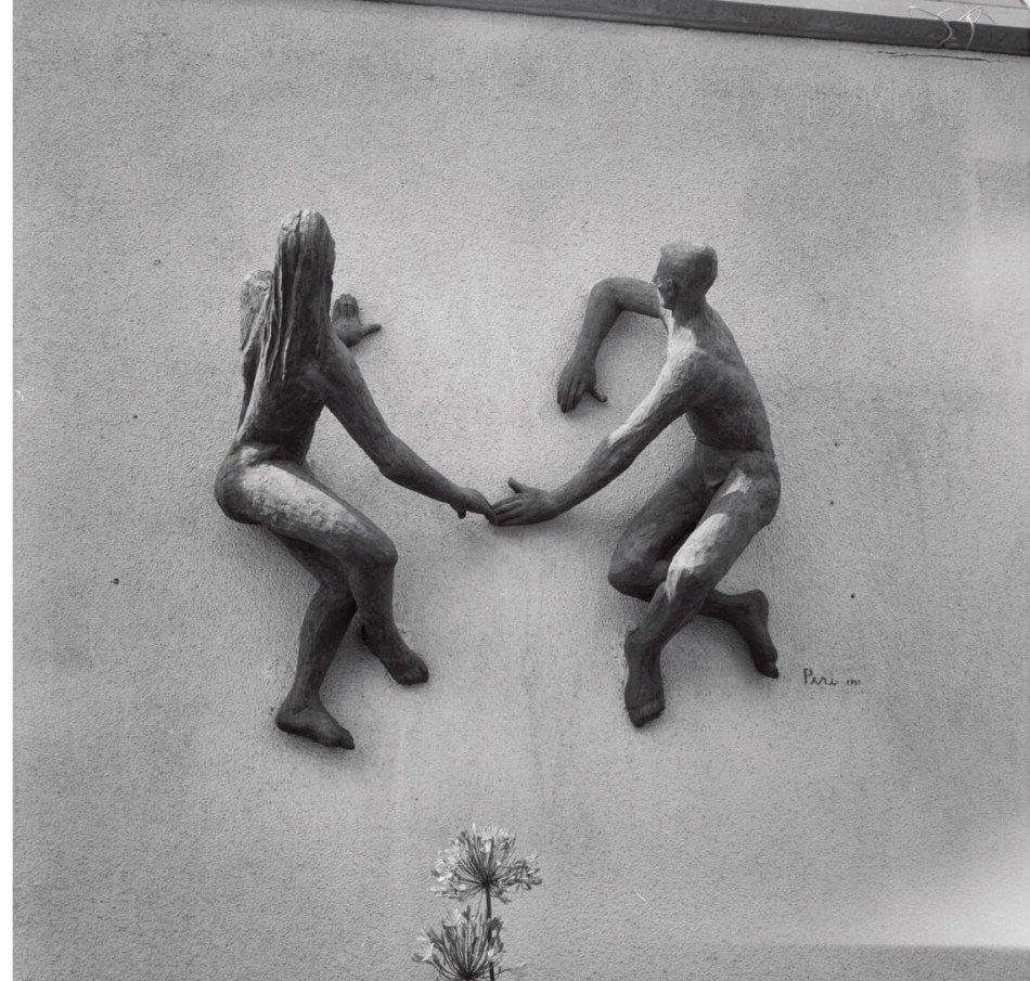 Two statues sunbathing, attached to the wall