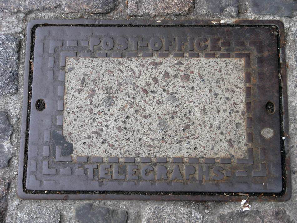 Manhole cover with 'Post office telegraphs' text along the top and bottom.